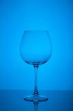 Pusty wina szkło na błękitnym tle Obraz Stock