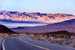 Pustynna droga w Śmiertelnej dolinie z halnym tłem Zdjęcia Stock