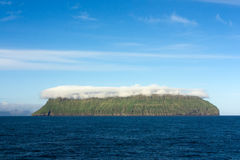 Pustynna zielona wyspa zakrywająca chmurą Obrazy Royalty Free
