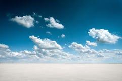 Pustynny krajobraz z głębokim niebieskim niebem i chmurami Obrazy Stock