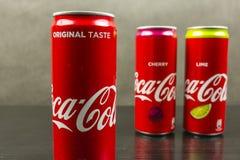 A puszka oryginalny smak koka-kola, w tło puszkach z smakiem wapno i wiśnia Obraz Royalty Free