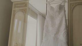 Puszysta ślubna suknia na wieszaku w pokoju hotelowym Ślubny ranek zdjęcie wideo