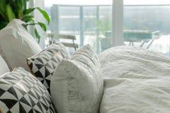Puszyste, dekoracyjne poduszki na istnym łóżku z marszczącymi prześcieradłami i akcentuacyjnymi kolorami, popielatymi, czar fotografia stock