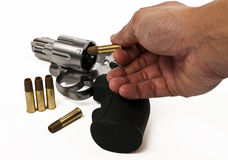 Put bullet into revolver gun Stock Images