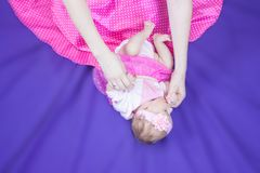 We put the child to sleep. Newborn in the mother& x27;s arms. girls in pink. horizontal orientation. happiness of motherhood Stock Photo