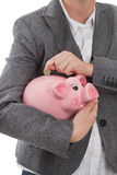 Put coin into piggy bank Royalty Free Stock Photos