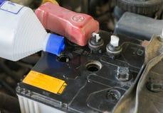 Put destillerade vatten in till batteribilen Arkivbild