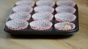Put the dough into paper cups. Hand pouring cake dough into muffin tray.  stock video footage