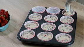 Put the dough into paper cups. Hand pouring cake dough into muffin tray.  stock video
