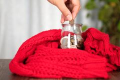 Put Euro coins into a glass bottle piggy bank wrapped in a red scarf