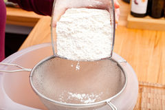 Put flour of glass bowl through a flour sieve Stock Photography