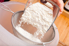 Put flour of glass bowl through a flour sieve Royalty Free Stock Photo