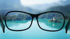 Put the glasses for the different, better view. Looking at the lake with the mountains. Stock Photos