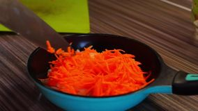 Put grated carrots in the pan stock footage