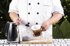 Put grinded cofffe into filter cup. Chef putting grinded cofffe into filter cup Stock Photos