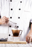 Put grinded cofffe into filter cup. Chef putting grinded cofffe into filter cup Stock Photography