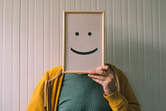 Put a happy optimistic face on, happiness and cheerful emotions. Put a happy face on, happiness and cheerful emotions concept, man holding picture frame with Royalty Free Stock Photography