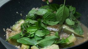 Put herbal green sweet basil leaves into the black teflon pan. For  stir fried  green sliced piece eggplants , minced pork , sliced garlic, chili shrimp paste stock video