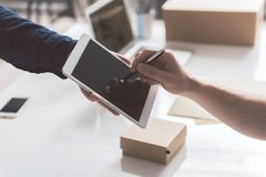 Male is receiving parcel at work. Put it here. Close-up of digital tablet in hand of courier and stylus in hand of young guy. Employee is appending his signature Stock Photo