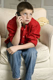 Put on hold. Teen boy sitting in chair put on hold on his cell phone Stock Photos
