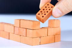 Put in the last brick. On a brick wall royalty free stock photography