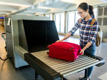 Put luggage at Point of checking the scanner. Beautiful woman chinese put luggage at Point of checking the scanner. Baggage X-ray machine band on the conveyor stock image