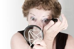 Put on Make-Up. Elderly woman putting on make-up royalty free stock image