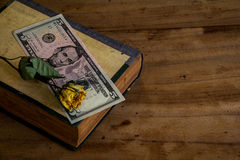 Put money on a book on old wooden floor.still life Stock Image