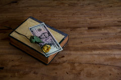 Put money on a book on old wooden floor.still life Royalty Free Stock Image