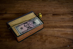 Put money on a book on old wooden floor.still life Royalty Free Stock Photo