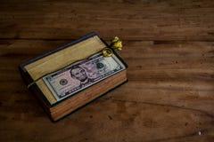 Put money on a book on old wooden floor.still life Stock Photos