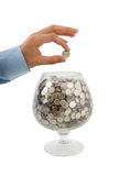 Put money into glass. Man's hand puts money into the glass Royalty Free Stock Photography