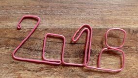 Put number 2018 of pink wire on a wooden table stock footage