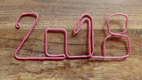 Put number 2018 of pink wire on a wooden table stock video