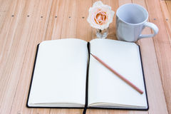 Put pencil on notebook near cup of coffee and rose Royalty Free Stock Photography