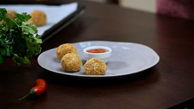 Put potato balls in a bowl stock video footage