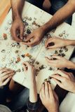 Overhead photo of Friends put Puzzle Together royalty free stock image
