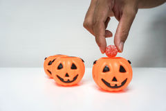 Put red candy into Jack-O-Lantern pumpkin for Halloween Stock Photography