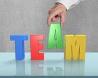 Put TEAM together on glass table Royalty Free Stock Image