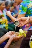Put water in the small bowl and then pour them into old woman`s. Hand Stock Photography