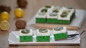 Put in white plate green soft cake with whipping cream and topping with kiwi. HD stock footage