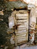 Put Wood in the Hole. Sorry excuse for a door, in a sorry excuse for a wall. The repair work is catastrophic, and the door is little more than a bundle of wood stock images