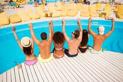 Put your hands up! Pool disco party. Six excited cheerful multi. Ethnic friends are chilling by the pool, sit on the nice wooden white floor, hold arms, luxure stock images
