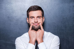 Put on your smile!. Handsome young man in formalwear holding fingers on his mouth and making fake smile while standing against blackboard Stock Photography