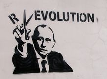 Putin and Revolution. Graffiti on the wall. President Putin cuts the letter off the word Revolution with scissors Stock Image