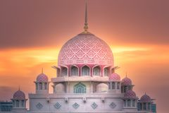 Putra Mosque with dramatic sky Putrajaya, Malaysia. Pink dome of Putra Mosque with sunshine of sunset on dramatic sky Putrajaya, Malaysia. Clipping path of sky stock photography