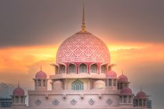 Putra Mosque with dramatic sky Putrajaya, Malaysia. Pink dome of Putra Mosque with sunshine of sunset on dramatic sky Putrajaya, Malaysia Royalty Free Stock Images