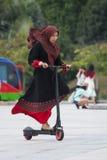 Putrajaya, Malaysia - circa September 2015: Malaysian girl in traditional dress and hijab is riding  scooter Stock Image