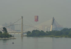 5th Putrajaya International Hot Air Balloon Fiesta 2013. PUTRAJAYA, MALAYSIA - MARCH 29:A hot air balloon passes by Seri Saujana Bridge during 5th Putrajaya stock images