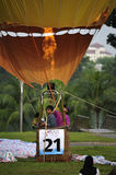 5th Putrajaya International Hot Air Balloon Fiesta. PUTRAJAYA, MALAYSIA - MARCH 29:Two tourists and a balloonist getting ready to ascend with the tethered hot stock photo